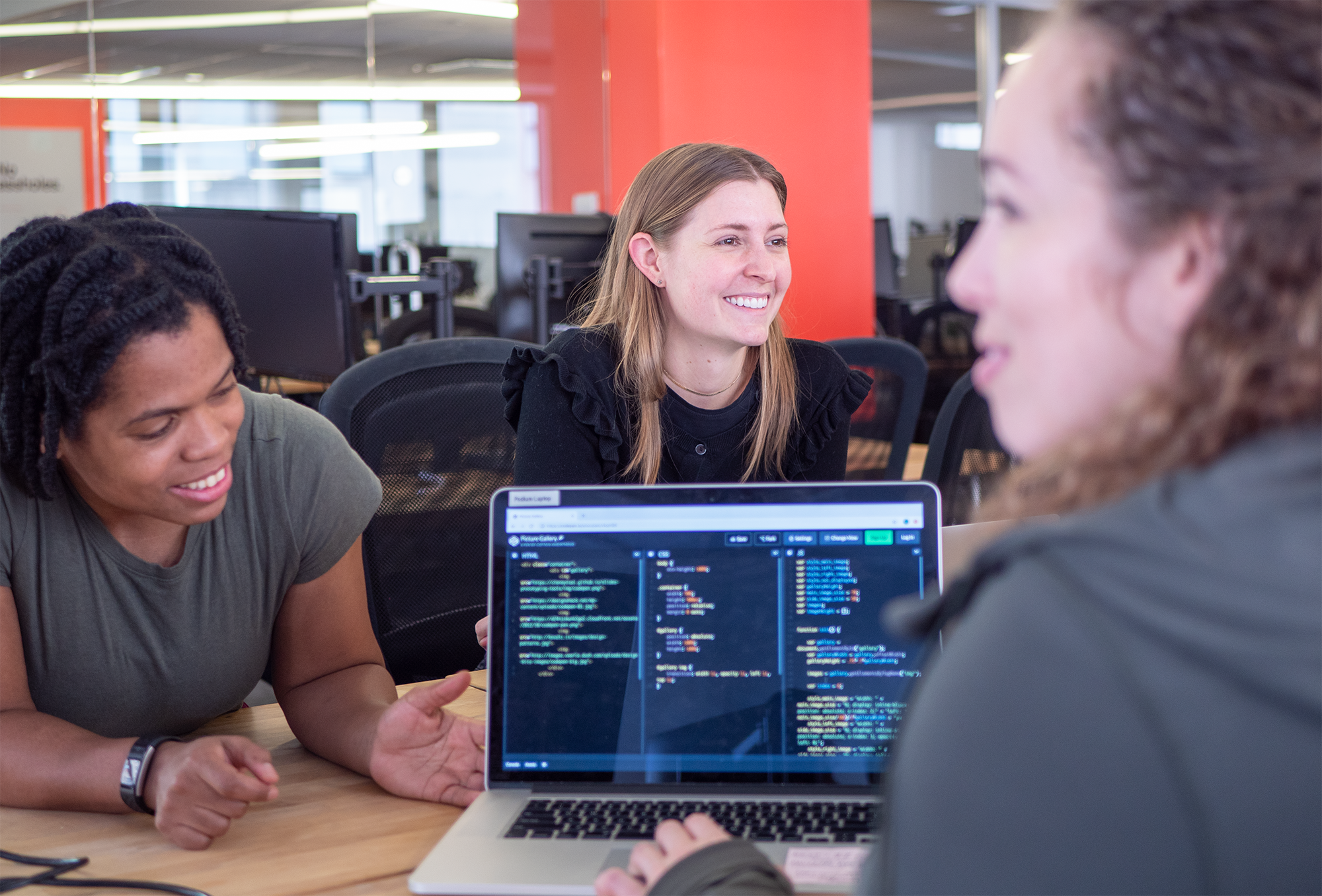 women-identifying students learning how to code