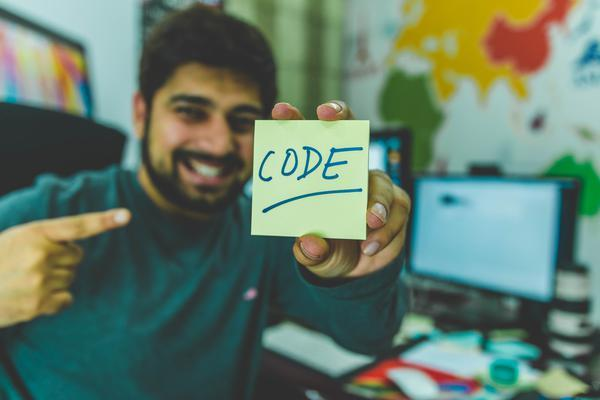 guy holding post-it note that says 'Code' because he loves javascript and other programming languages