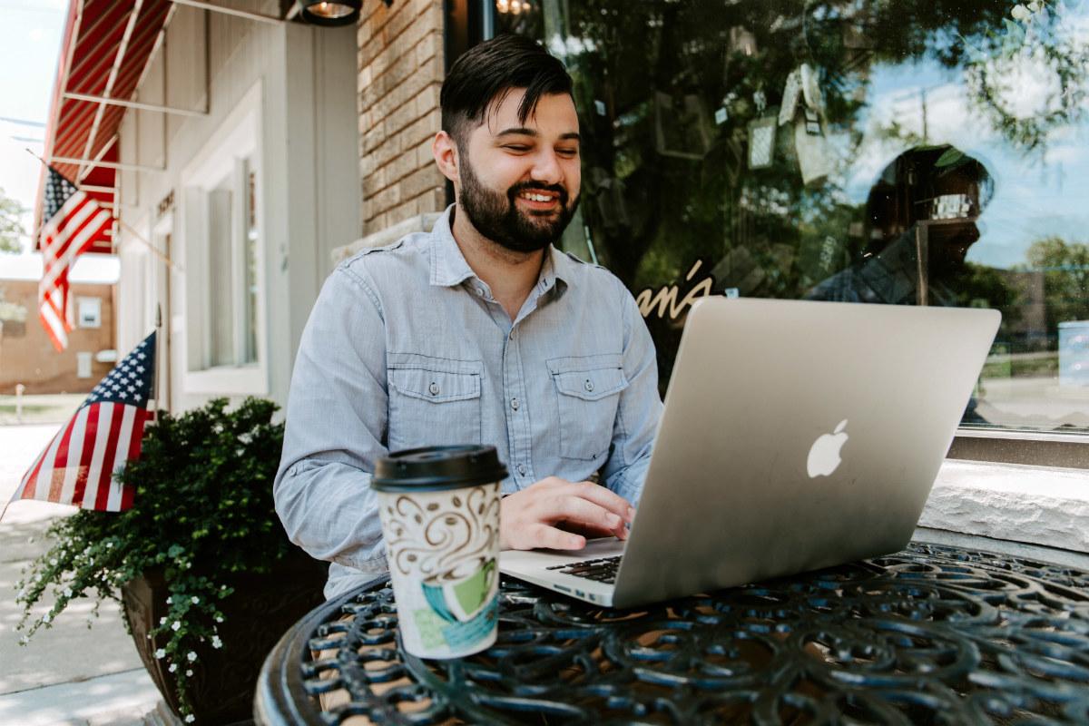 Man job seeking on at laptop investigating a career change