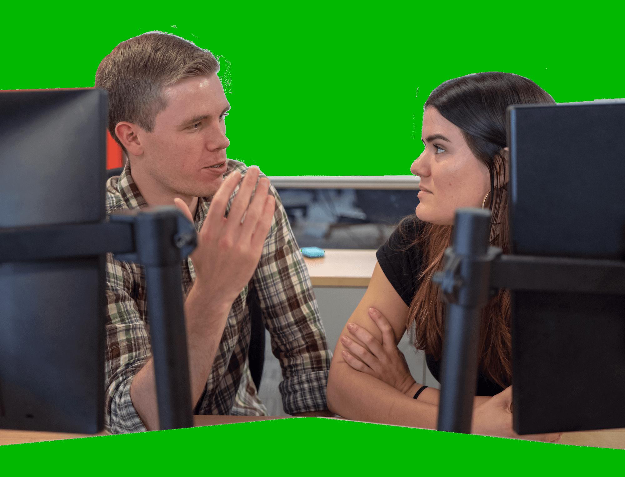 Man and woman talking behind computers