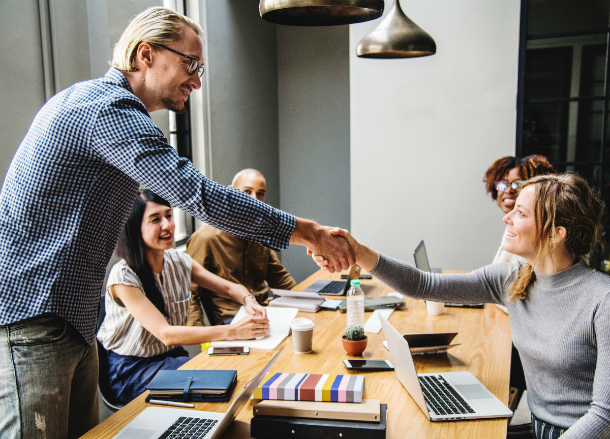 Woman shaking hands with man after negotiating job offer