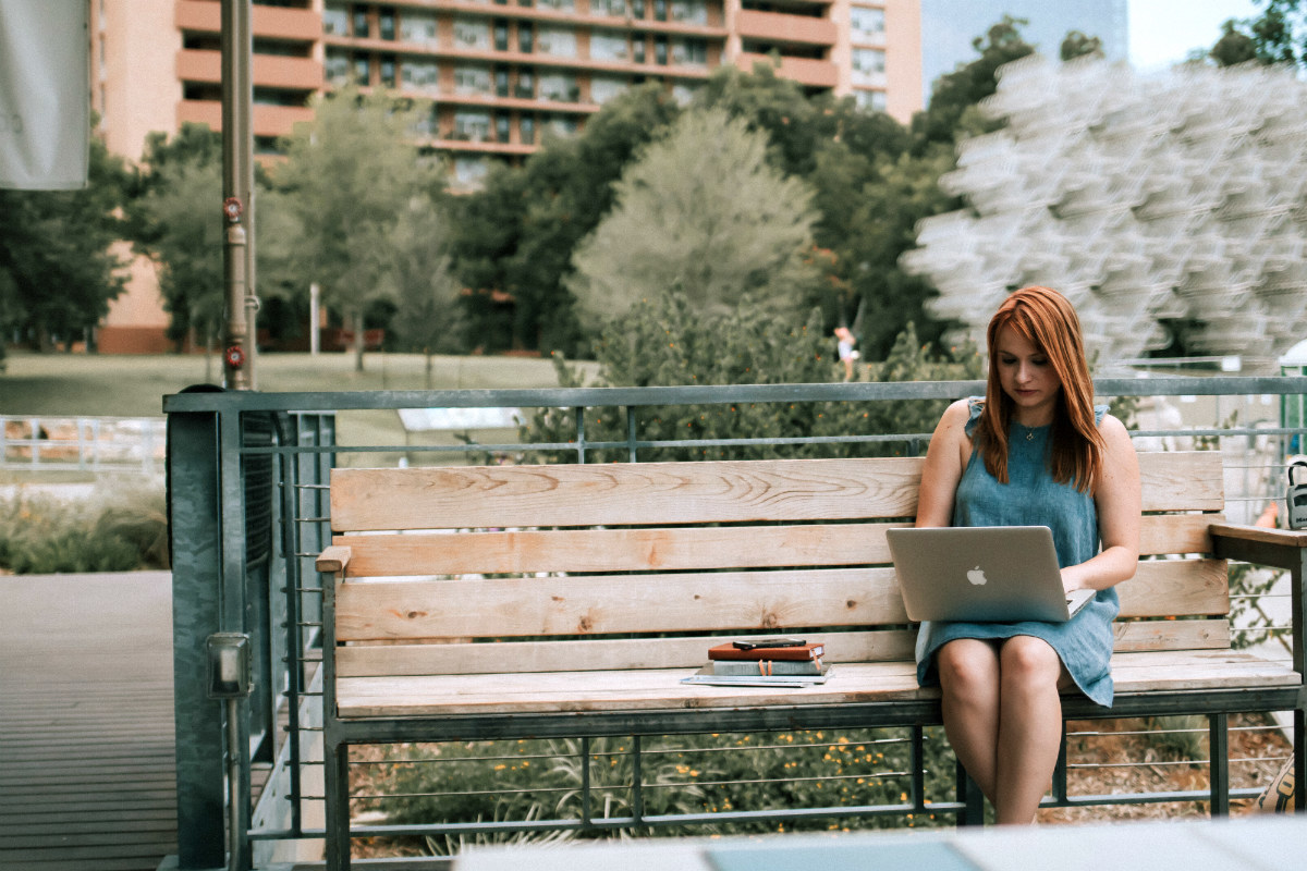 Woman using her laptop in a park, planning a career change
