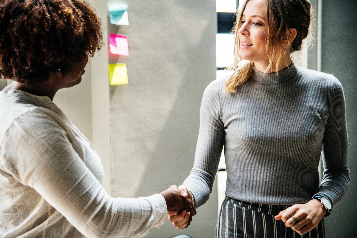 Handshake between two woman, representing solidarity against workplace sexisim