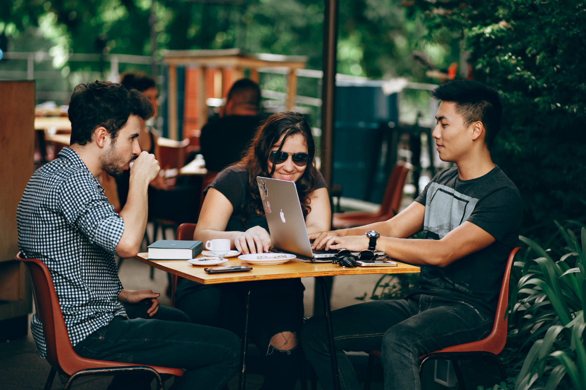 Three young people with laptops at a cafe discuss their first job after coding bootcamp