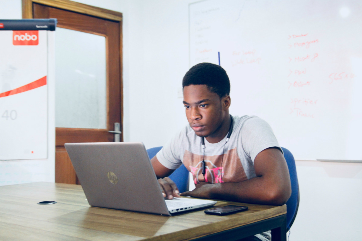 Coder of color at a laptop celebrating Black coders in tech