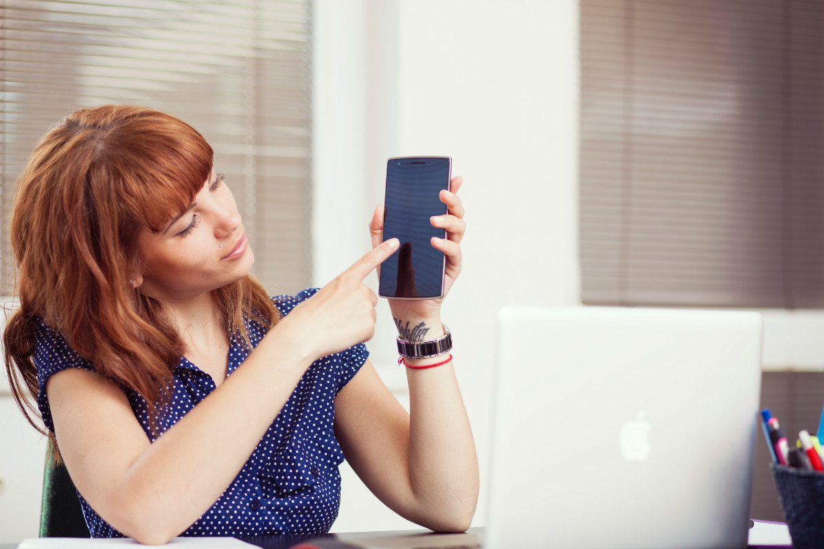 Woman hold a smartphone, representing workplace sexism