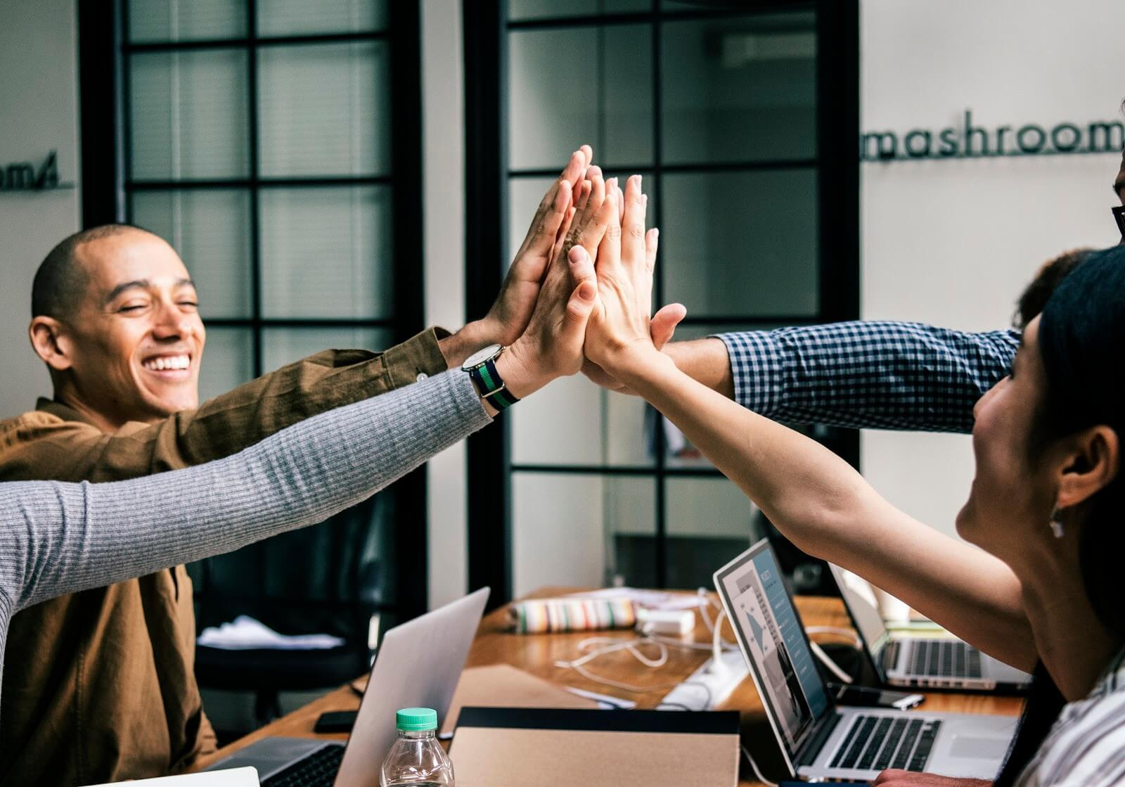 Four coders giving high fives representing an answer to the question - Are coding bootcamps worth it?