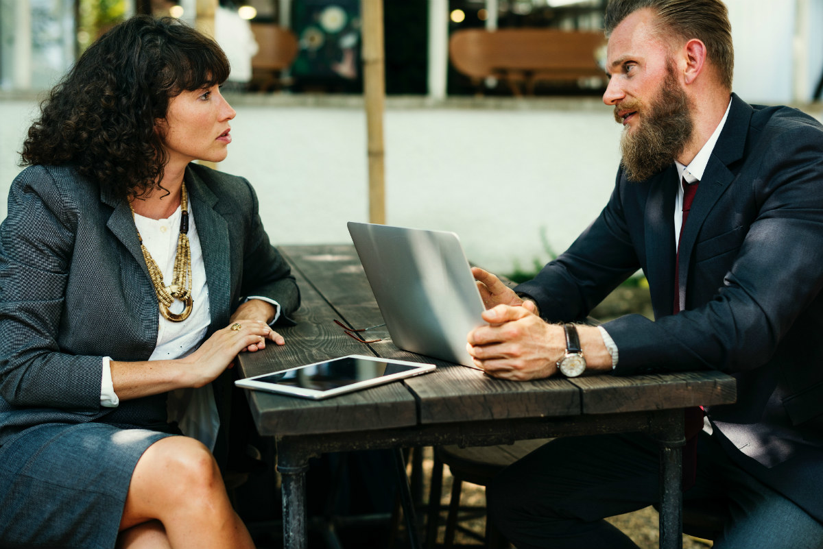 Two professionals, the man looks dismissively at the woman, representing the gender gap in tech