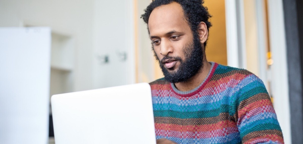 Man In Sweater Looking At Screen