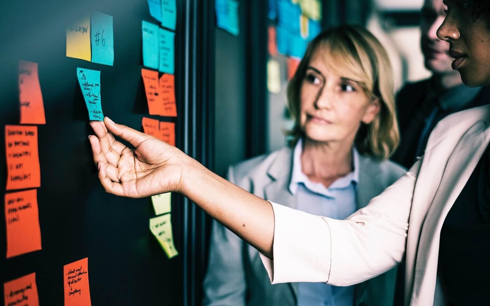 Older woman looks at younger colleague holding Post-It note