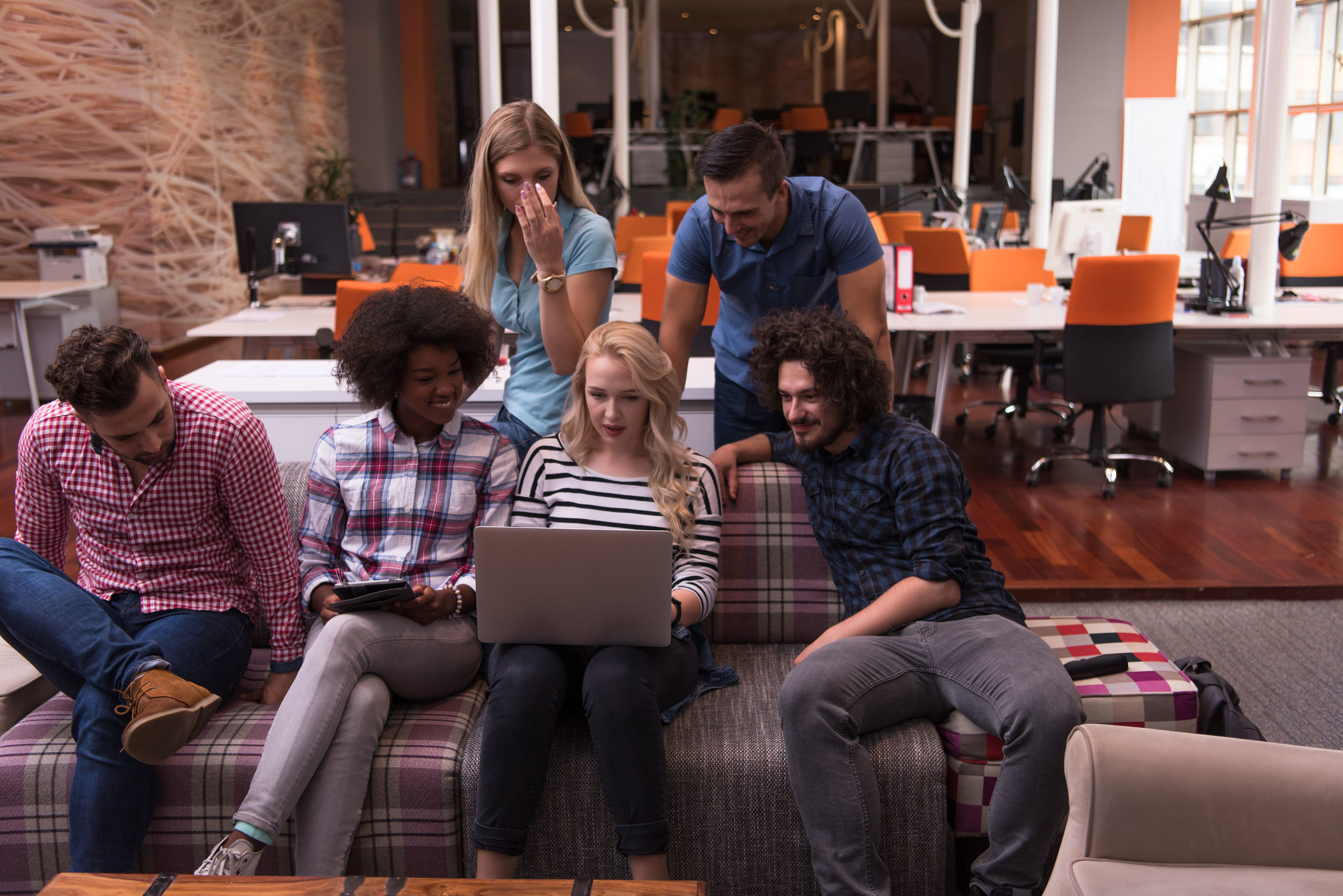 A diverse team around a laptop, illustrating the gender gap in tech