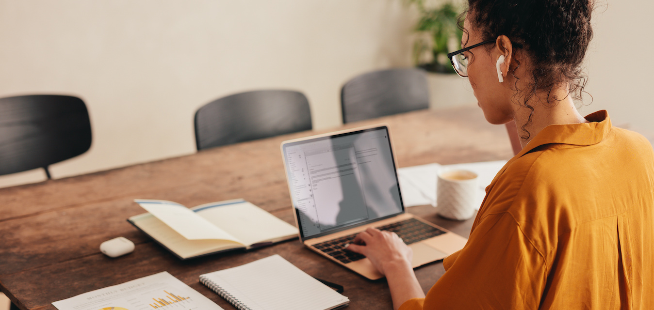 Female Data Analyst Working At Laptop With Paper